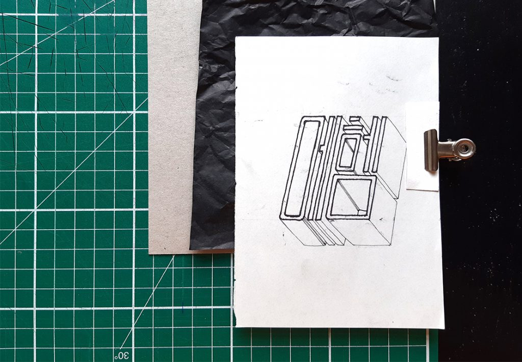Sketch and carbon paper clipped to cardboard