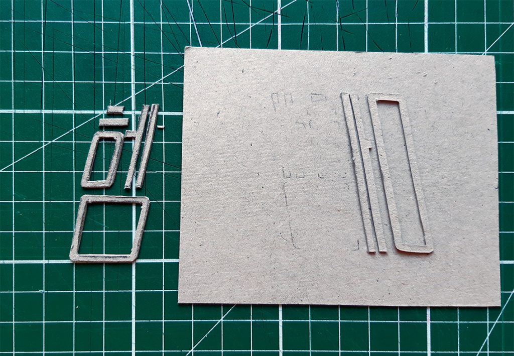 Sticking the elements of the cut out onto a base, wrong-reading