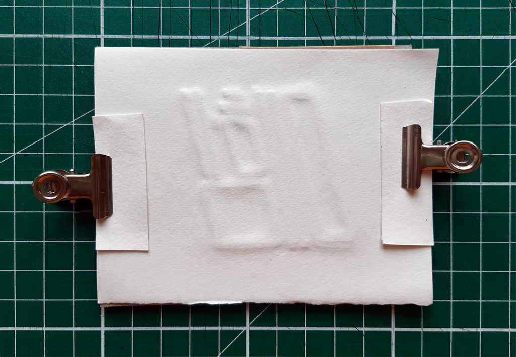 damp paper secured to base with clips, strips of card under clips prevent damage to paper