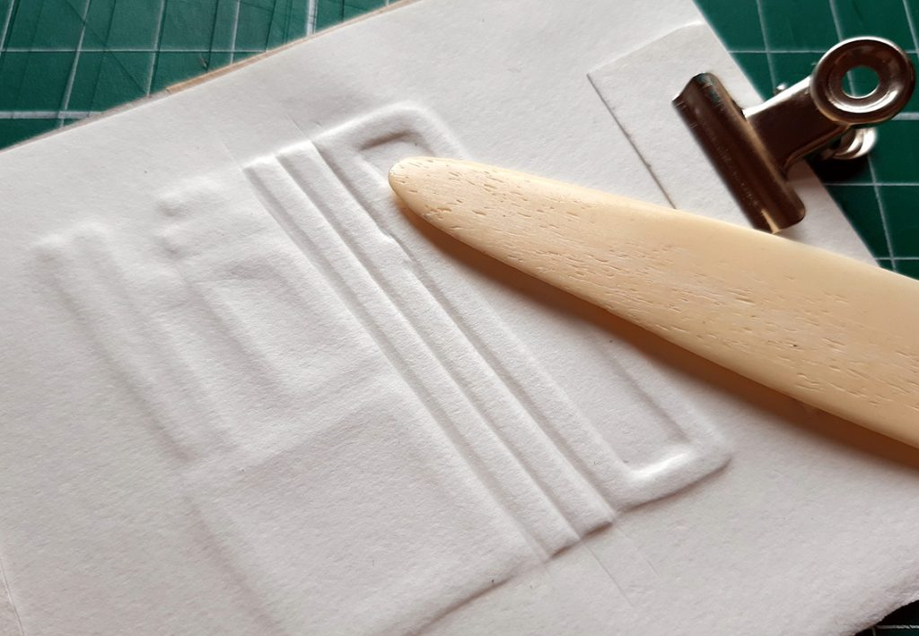 Using bone folder to mould paper around cut outs, creating embossed shape