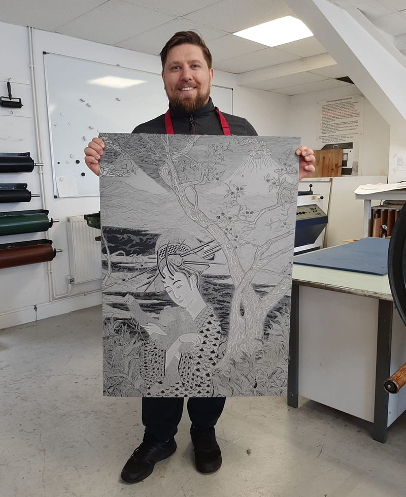 Photograph of Vito at Thames-Side Print Studio, holding a lino block, in front of a press.