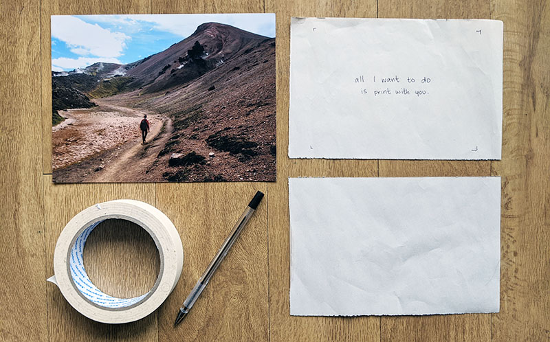 Clockwise from top left: photograph, text written by hand on paper, blank paper, ballpoint pen, roll of masking tape