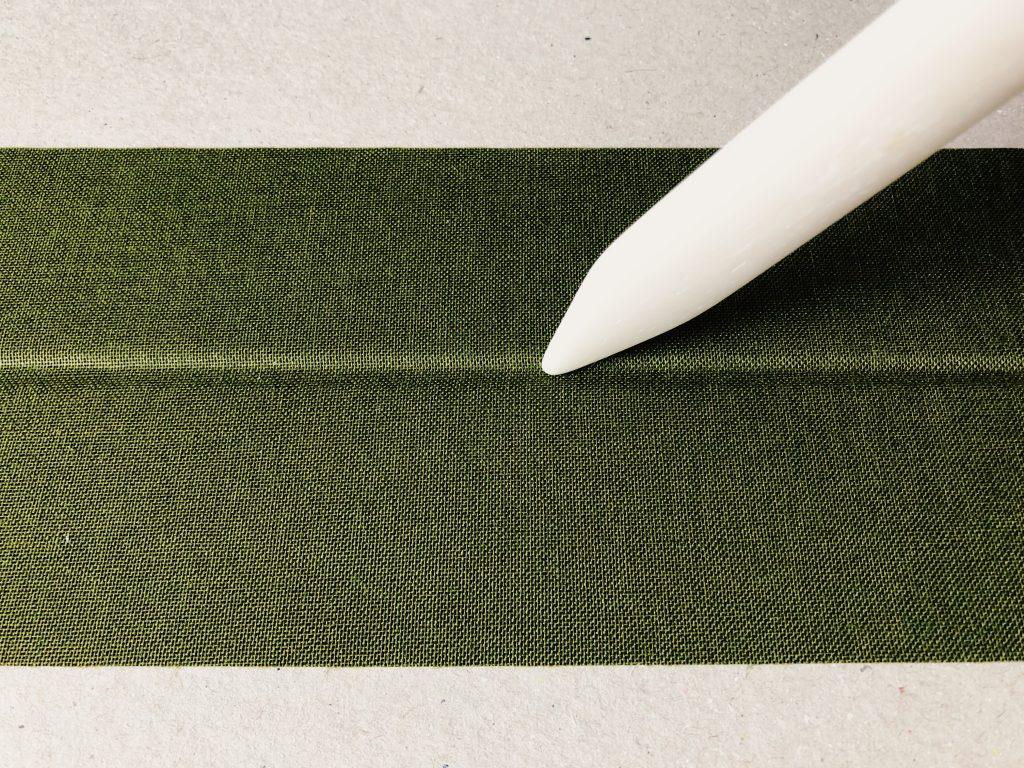 Image of the usage of a bone folder