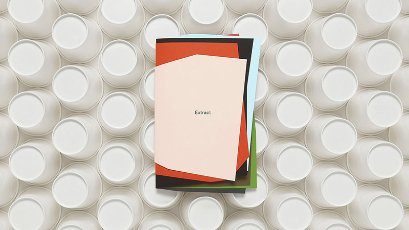 This image shows G F Smith, Extract paper swatch book on top of empty paper cups