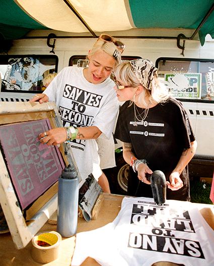 image of rosie and maeve screenprinting at Glastonbury festival . ©photo by Alex Kurunis
