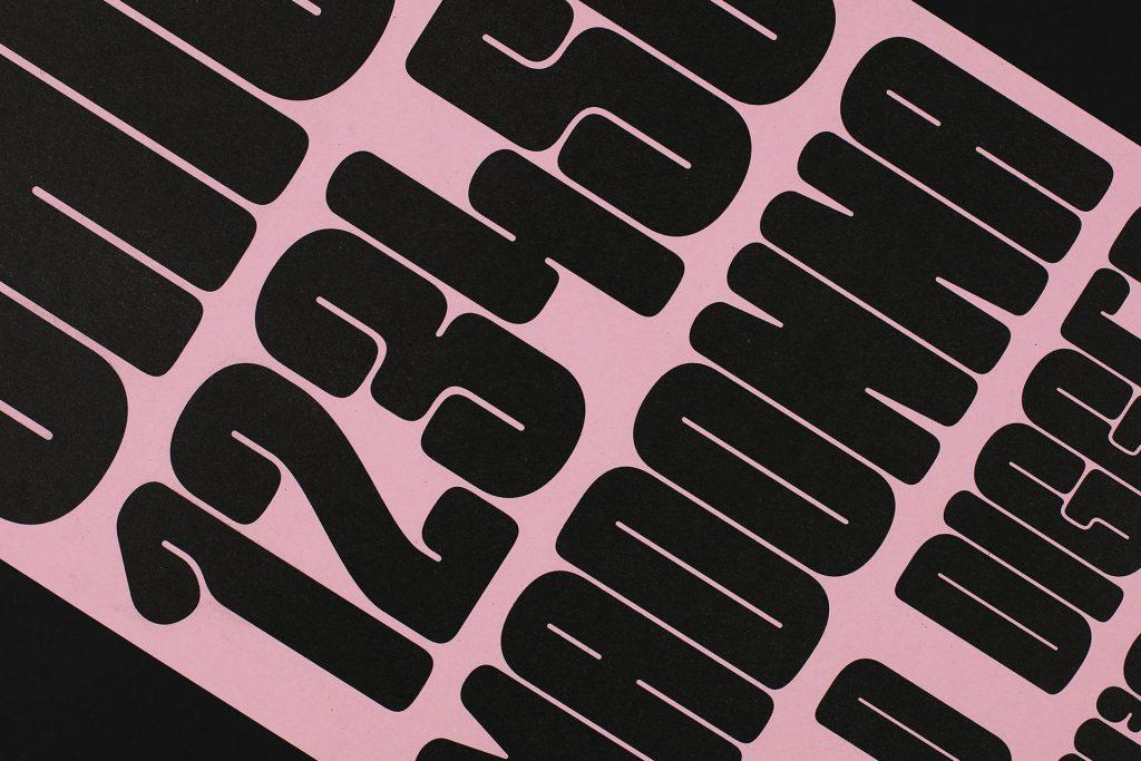 Close up of letterpress printed Good Girl type specimen, black on pink paper