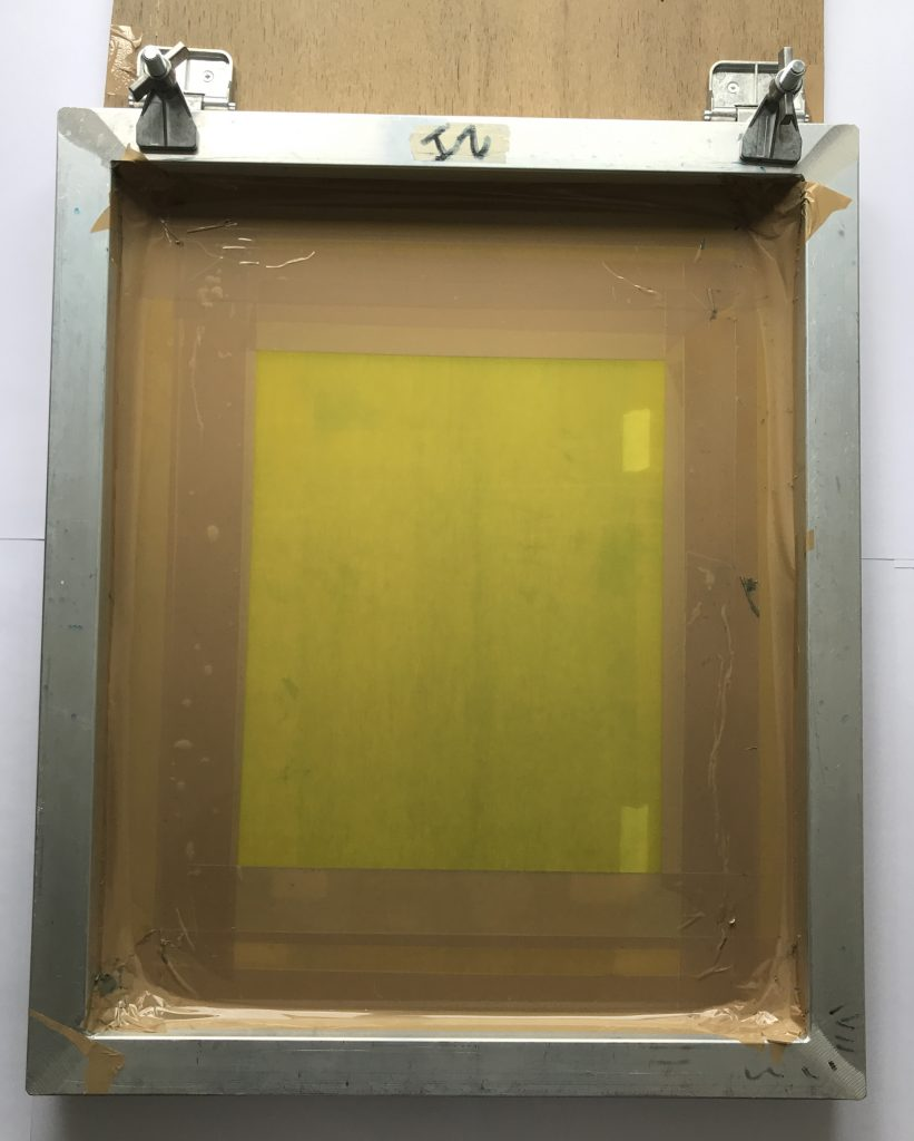 Screen attached to wood with clamps, with tape creating a 'window'