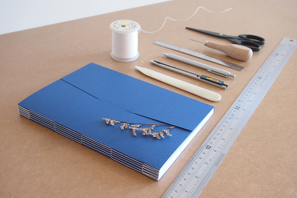 Image is showing a Long Stitch Binding and all materials required for making it: awl, bone folder, needle, thread, cutting knife, pencil, ruler cutting mat, eraser, scissors