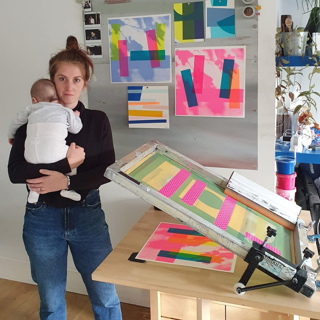 Josie holding her baby next to an improvised screen printing bed
