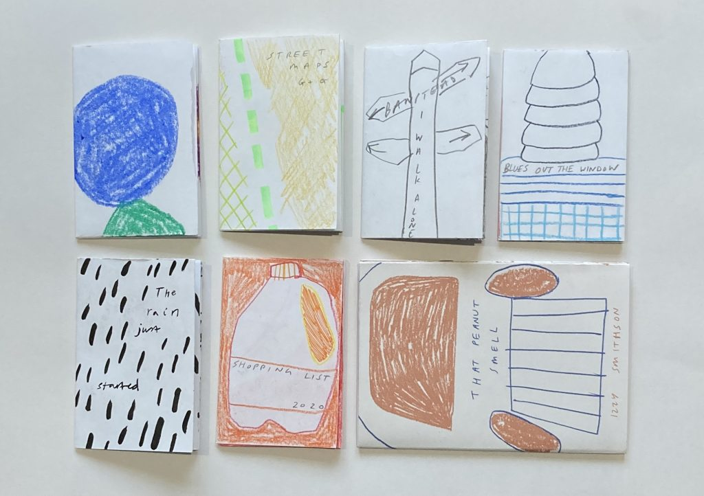 A group of zines on a table, all hand drawn with colourful pencils.