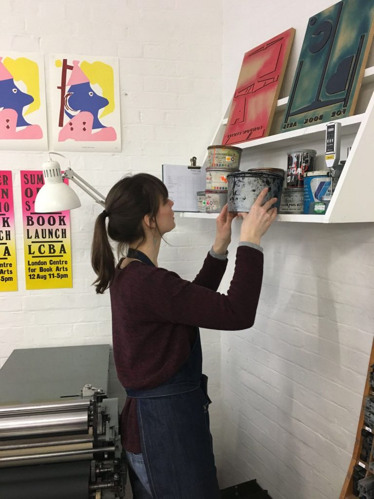 Julia Blom picking up a can of ink from a shelf.