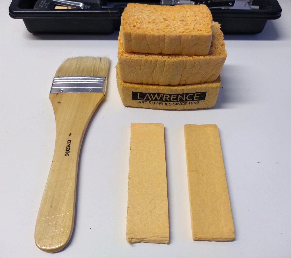 Sponges and brushes. Image shows a large flat brush and sponges compressed and hydrated.