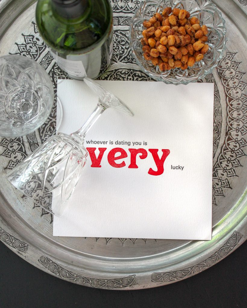Letterpress print reading 'whoever is dating you is very lucky', on a silver tray with wine glasses and nuts.