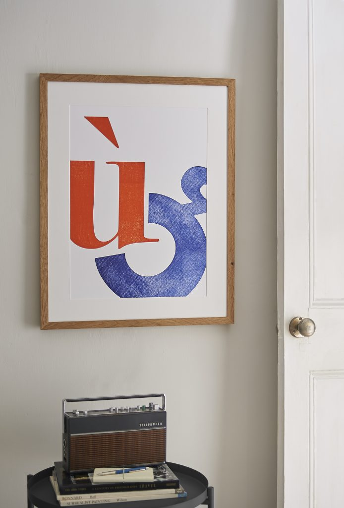 Framed letterpress print. Two large characters printed in orange and blue. Hanging on a wall above a coffee table and radio.