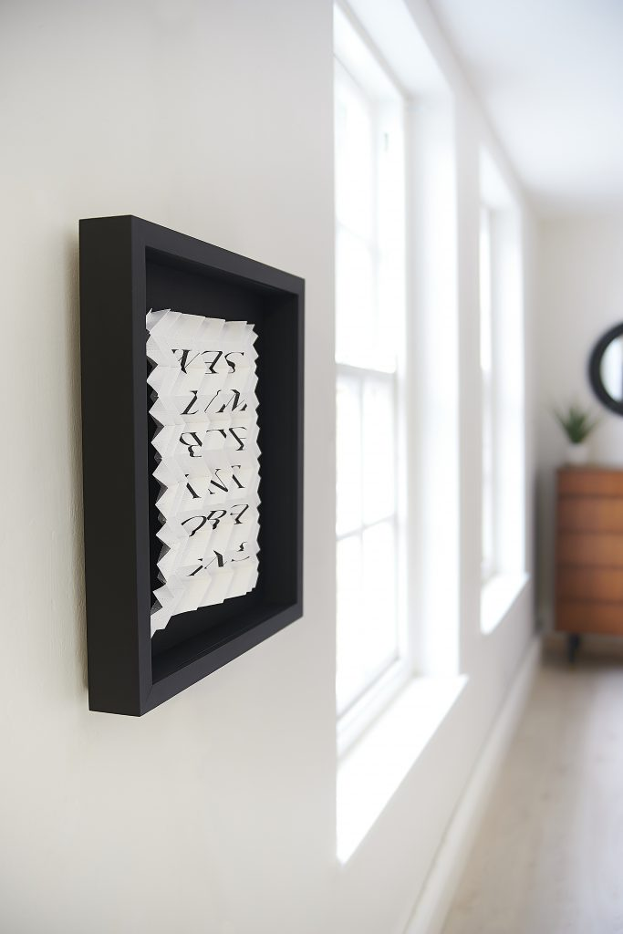 Framed letterpress print. The print is folded intricately and hangs in a square black frame. Viewed at an angle.