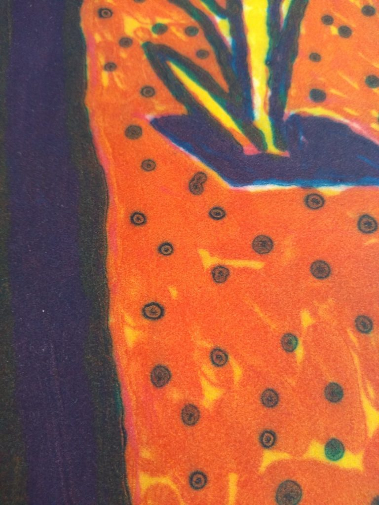 Close up of textured area in the print of blue dots on a textured orange and yellow field