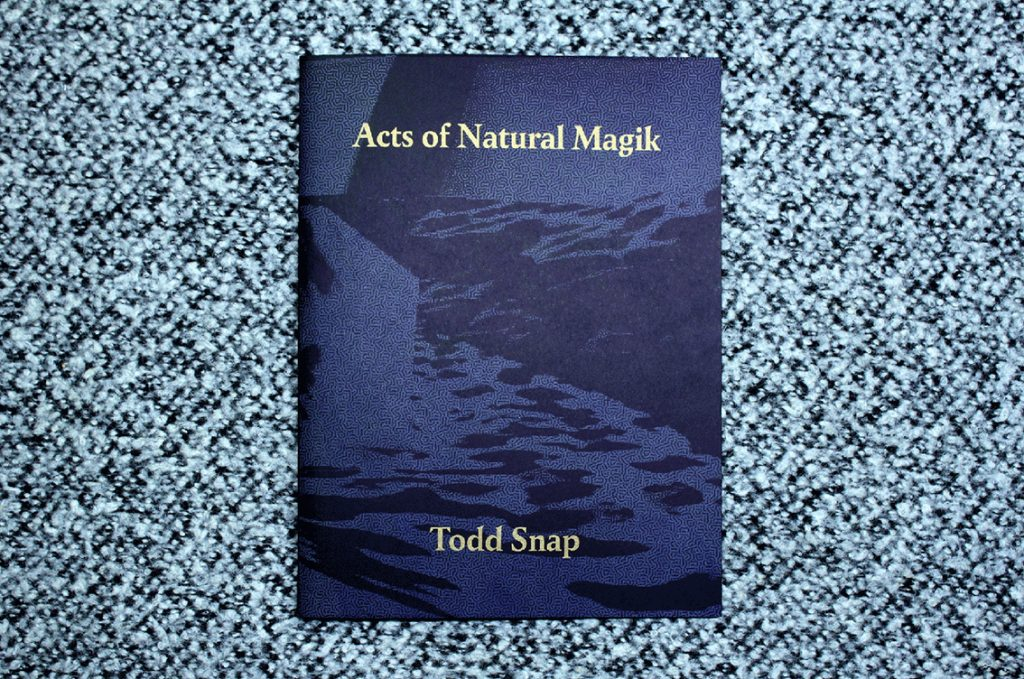 Publication cover in two tones of dark blue with the text Acts of Natural Magik and Todd Snap in gold