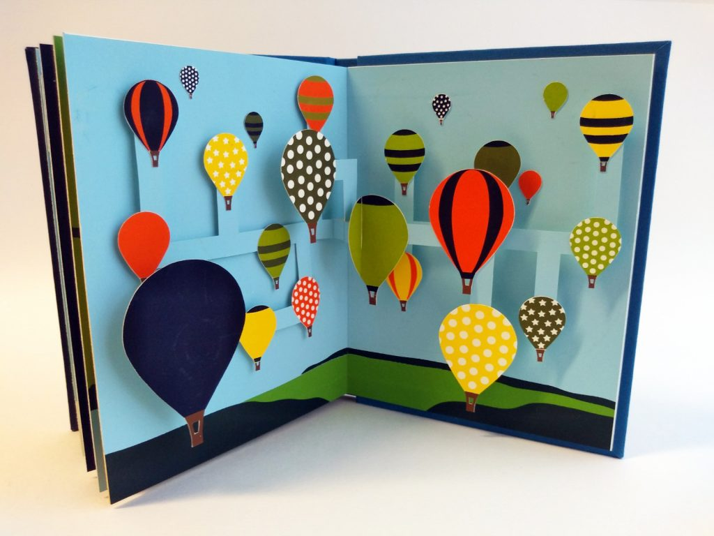 Open page of a book depicting a large group of hot air balloons, of different sizes, colour and pattern. Some of the hot air balloons are pop-up and appear to float as the stick up from the page.