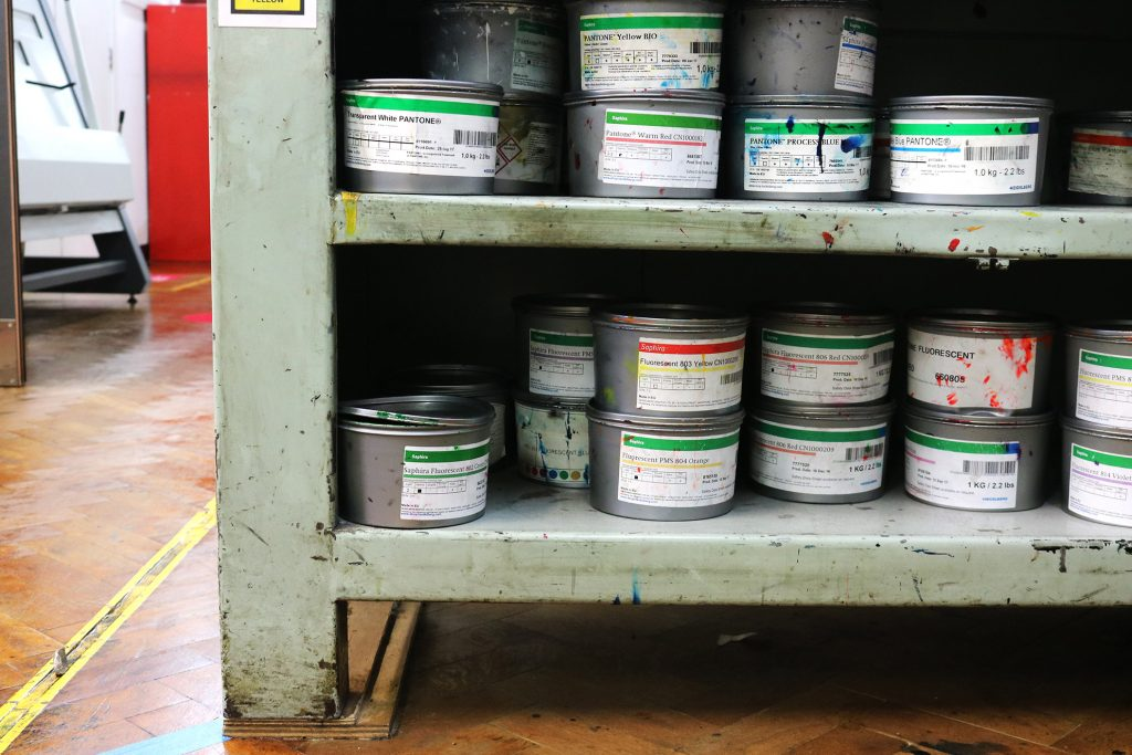 Shelves underneath the galley proofing press in letterpress, showing tins of Saphira Pantone inks.