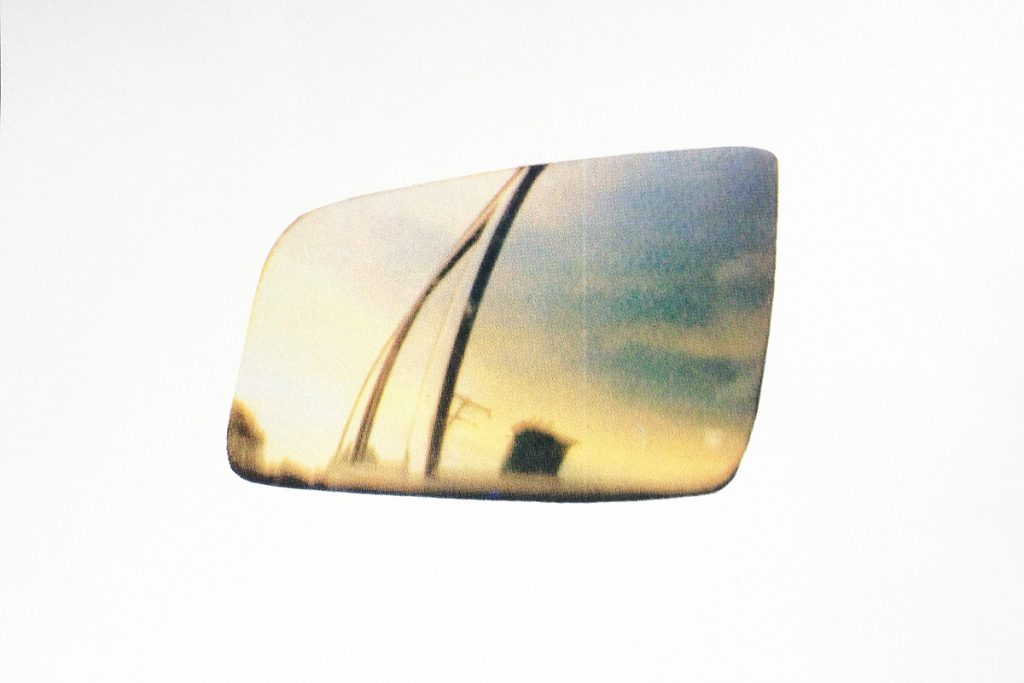 View of the sky with clouds and sunlight and the reflection of a car. The image is the shape of a side mirror.