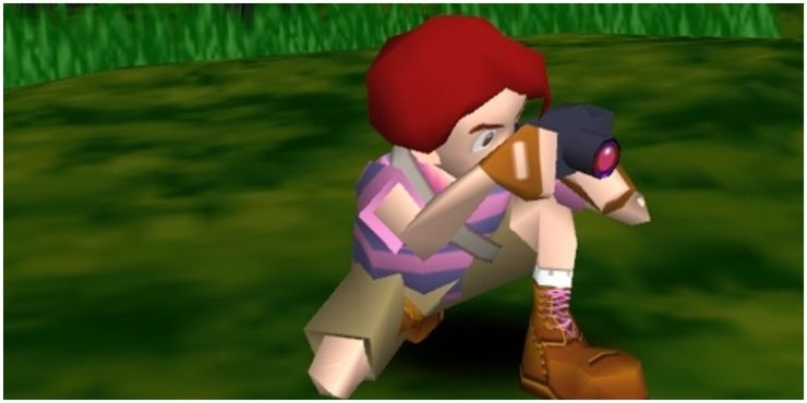 Low-resolution graphic of a person with a camera and red hair, crouching on the ground taking a photograph off screen